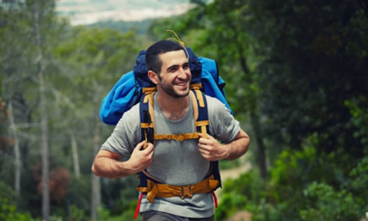 man carrying backpack and trekking